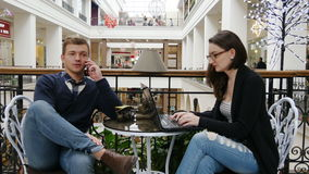 Gelukkig paar met smartphone en laptop in koffie Man die op telefoon, vrouw spreken die aan notitieboekje bij koffie in het winke stock videobeelden