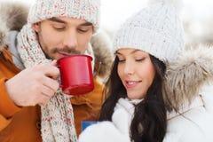 Gelukkig paar met theekoppen over de winterlandschap Stock Foto's