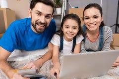 Gelukkig paar met weinig dochter die op bellenomslag, die laptop het scherm bekijken in het herstellen van huis liggen stock fotografie