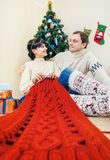 Gelukkig paar onder Kerstmisboom met het breien van het werk Stock Foto's