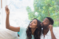 Gelukkig paar op de laag die selfie nemen stock fotografie