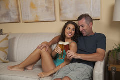Gelukkig paar op de laag die van een koud bier genieten Stock Afbeeldingen