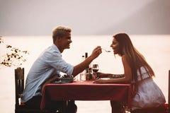 Gelukkig paar op de zomeravond die romantisch diner hebben openlucht stock afbeelding