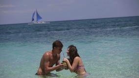 Gelukkig paar op het strand met kokosnoot stock footage