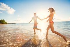 Gelukkig Paar op Tropisch Strand bij Zonsondergang stock foto's