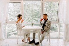 _gelukkig paar in restaurant kijken elkaar en roosteren Stock Afbeelding