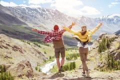 Gelukkig paar tegen bergen opgeheven handen stock fotografie