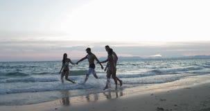 Gelukkig Paar twee die op de Handen van de Strandholding bij Zonsondergang, de Mededeling van Jongerentoeristen lopen over de Zom stock videobeelden