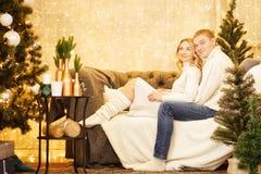Gelukkig paar van minnaars in truien die Kerstboom verfraaien Kerstmis en nieuw jaar thuis Jonge Familie samen Royalty-vrije Stock Foto's