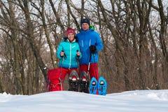 Gelukkig paar van wandelaarstribunes in een de winterbos naast snowsho Stock Foto