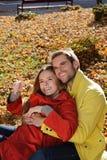 Gelukkig Paar in zonnig Autumn Park Daling Jonge familie die pret hebben in openlucht Gele Bomen en Bladeren Lachende Man en Vrou Stock Foto