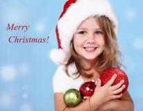 Gelukkig peutermeisje in de hoed van de Kerstman stock afbeeldingen