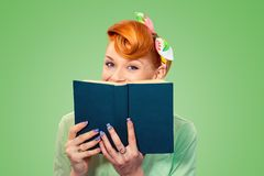 Gelukkig pinupmeisje die verbergen achter een boek royalty-vrije stock afbeelding
