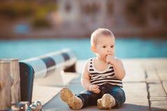 Gelukkig portret van weinig jongen die in openlucht bij dok dichtbij het overzees spelen stock afbeelding