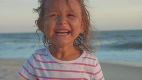 Gelukkig portret van weinig kindmeisje die camera bekijken en bij strand lachen stock video