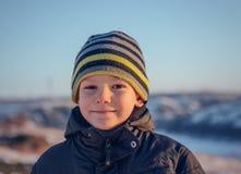 Gelukkig portret weinig kleding die van de jongenswinter pret in verse witte de wintersneeuw hebben in avondlicht royalty-vrije stock afbeelding