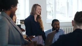 Gelukkig positief die het jonge chef- vrouw genieten glimlachen die met multi-etnische partners op modern licht kantoor werken stock footage