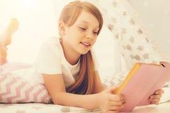 Gelukkig positief meisje die een verhaal lezen stock fotografie