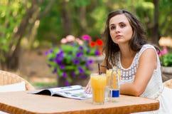 Gelukkig, positief, mooi, de zitting van het elegantiemeisje bij koffielijst in openlucht Royalty-vrije Stock Foto