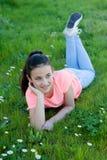 Gelukkig preteen meisje liggend in het gras Royalty-vrije Stock Foto's