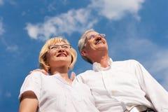 Gelukkig rijp paar dat aan de blauwe hemel kijkt Royalty-vrije Stock Afbeeldingen