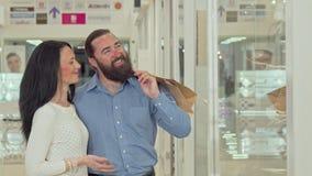 Gelukkig rijp paar die de showcase van de kledingsopslag bij het winkelcomplex bekijken stock videobeelden