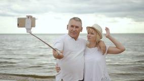 Gelukkig rijp paar die en selfie op kust kussen doen stock videobeelden