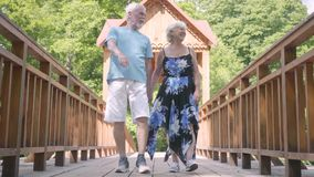 Gelukkig rijp paar die op de handen van de brugholding lopen Elegante hogere vrouw in de zomerkleding en haar echtgenoot het best stock videobeelden