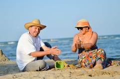 Gelukkig rijp paar die pretzitting hebben bij kust op zandig strand Stock Foto