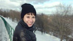 Gelukkig Romantisch Meisje die en bij Camera in Sneeuwpark bekijken nemen Spontaan Portret van Glimlachende Vrouw in openlucht in stock videobeelden