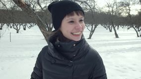 Gelukkig Romantisch Meisje die en bij Camera in Sneeuwpark bekijken nemen Spontaan Portret van Glimlachende Vrouw in openlucht in stock footage