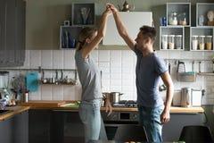 Gelukkig romantisch paar die in de keuken dansen terwijl het koken toget stock foto