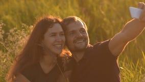 Gelukkig romantisch paar die in het Park bij zonsondergang lopen en een selfie nemen Een jonge mens na een selfie die zijn meisje stock video