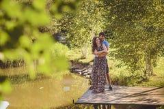 Gelukkig romantisch paar op een houten brug dichtbij het meer De man omhelst een jonge vrouw, hebben zij pret het lachen Royalty-vrije Stock Foto