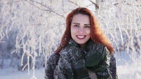 Gelukkig roodharig meisje die tegen een snow-covered boom in een de winterbos glimlachen stock videobeelden
