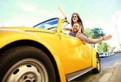 Gelukkig samen te reizen Blij jong paar die terwijl het berijden in onvertible glimlachen stock foto