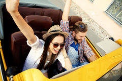 Gelukkig samen te reizen Blij jong paar die terwijl het berijden in onvertible glimlachen royalty-vrije stock foto's