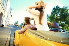 Gelukkig samen te reizen Blij jong paar die terwijl het berijden in onvertible glimlachen stock foto's