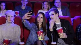 Gelukkig schitterend jong meisje die een selfie met haar vriend in de bioskoop nemen stock videobeelden