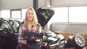 Gelukkig schitterend meisje die computerdiagnostiek gebruiken terwijl het herstellen van auto stock videobeelden