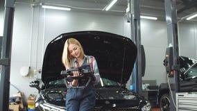 Gelukkig schitterend meisje die computerdiagnostiek gebruiken terwijl het herstellen van auto stock footage