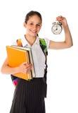 Gelukkig schoolmeisje die zich met boek en wekker bevinden Royalty-vrije Stock Foto's