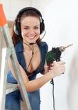 Gelukkig seksueel meisje in hoofdtelefoons met boor stock fotografie