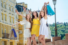 Gelukkig shopaholicsmeisje Drie meisjes die het winkelen houden stock foto
