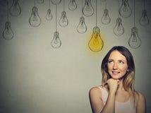 Gelukkig slim meisje met oplossing lightbulb boven hoofd royalty-vrije stock fotografie