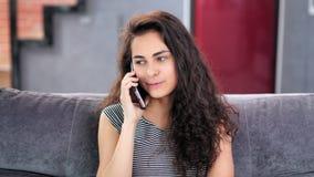 Gelukkig Spaans roddelmeisje die genietend van het spreken gebruikend smartphone thuis middelgroot close-up glimlachen stock footage