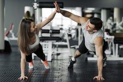 Gelukkig sportief paar die hoogte vijf geven aan elkaar terwijl omhoog samen het doen van duw in gymnastiek Eenheid en steun, exe stock foto's