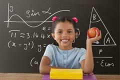 Gelukkig studentenmeisje die bij lijst een appel houden tegen grijs bord met onderwijs en schoolgrafiek royalty-vrije stock foto's