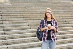 Gelukkig studentenmeisje die met koffiekop zich in openlucht bevinden Stock Foto