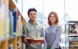Gelukkig studentenpaar met boeken in bibliotheek Stock Foto's